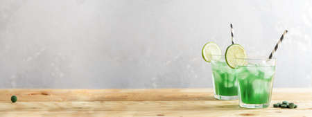 Two glasses of refreshing lemonade with chlorella and lime on a wooden table. Stock Photo