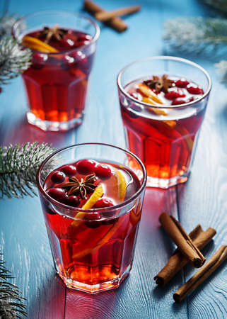 Festive mulled wine with lingonberry on a blue wooden table. Glasses of mulled wine.