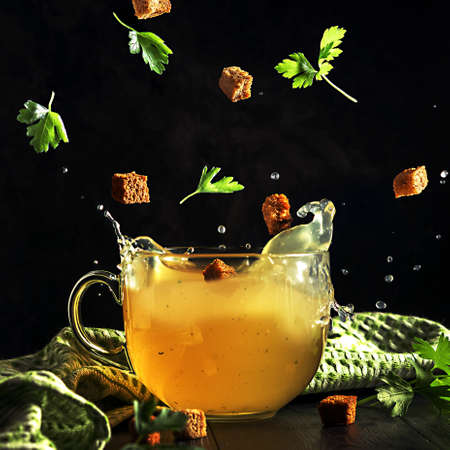 A cup of broth with flying ingredients and splashes on a dark background.