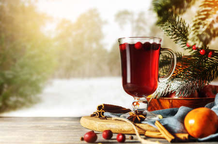 Glass of mulled wine with ingredients on a wooden table against the background of winter forest.
