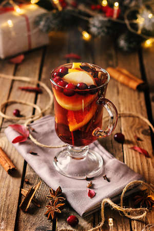 Glass of mulled wine with ingredients on a wooden table with a copy of space.