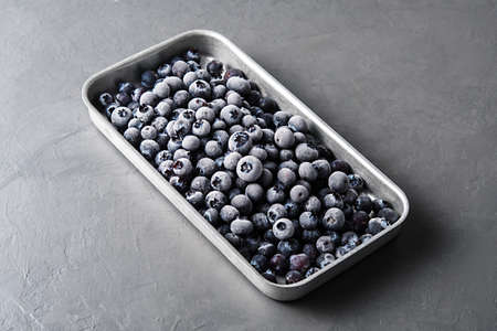 Frozen blueberries in a metal tray on a concrete background.