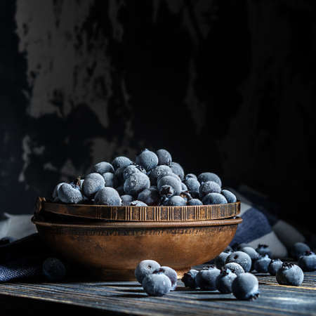 Frozen blueberries in a retro cup on a wooden table. 免版税图像