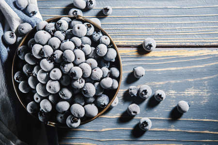 Frozen blueberries in a retro cup on a wooden table. Top view.