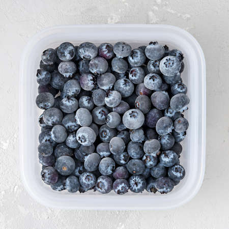 Frozen blueberries in the tray on a concrete background.