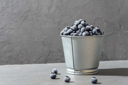 Frozen blueberries in a metal pot on a concrete background.