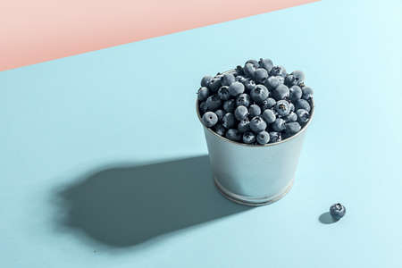 Frozen blueberries in a metal pot against a blue background. 免版税图像 - 154763813