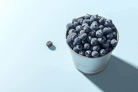 Frozen blueberries in a metal pot against a blue background. 免版税图像