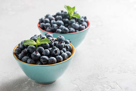 Fresh blueberries in bowls on a concrete surface with a copy of space. 免版税图像 - 155404864