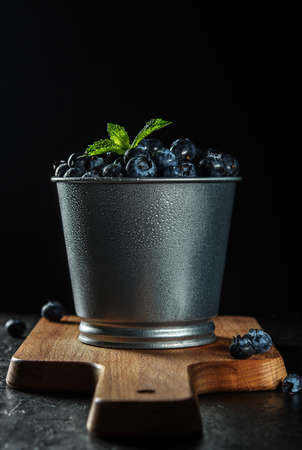 Fresh blueberries in a metal pot against a dark background.
