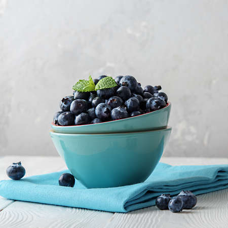 Fresh blueberries in a blue bowl on a light wooden table. 免版税图像 - 155404909