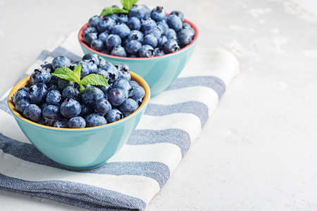 Fresh blueberries in bowls on a concrete surface with a copy of space.