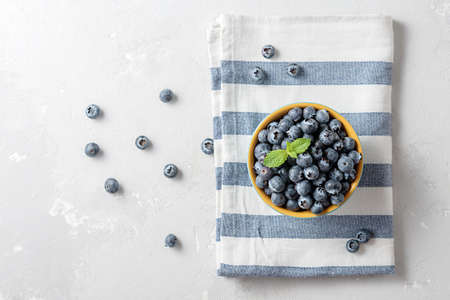 Bowl of blueberries with striped textile on the concrete table with a copy of the space.