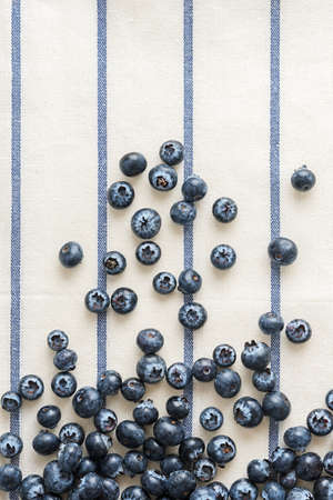 Fresh blueberries on striped textile with a copy of space.