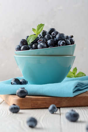 Fresh blueberries in a blue bowl on a light wooden table. 免版税图像