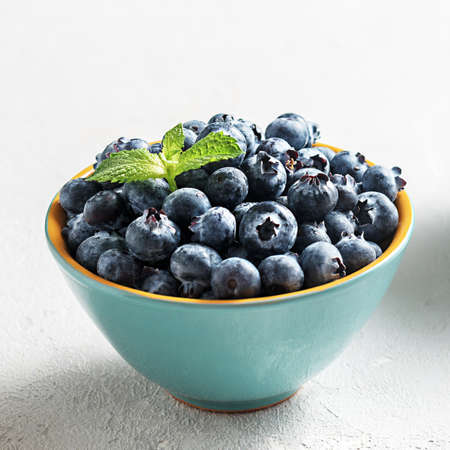 Fresh blueberries in a bowl on a concrete surface. 免版税图像 - 155405090