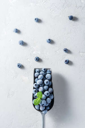 A scoop of frozen blueberries on a concrete surface. 免版税图像 - 155405099