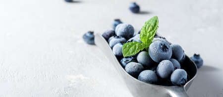 A scoop of frozen blueberries on a concrete surface. 免版税图像 - 155368191