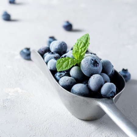A scoop of frozen blueberries on a concrete surface.