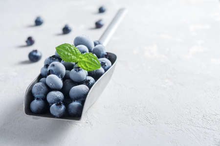 A scoop of frozen blueberries on a concrete surface. 免版税图像 - 155368187