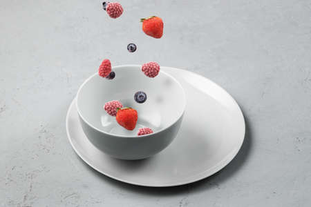 Frozen berries fall into a gray bowl.