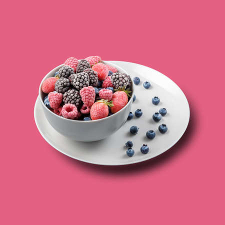 Frozen berries in a gray bowl against a pink background. 免版税图像 - 155682551