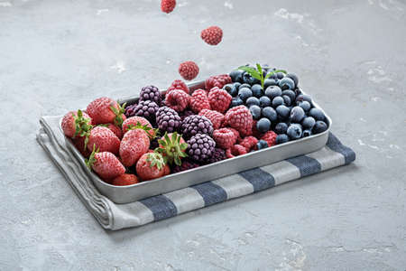Frozen berries fall into the tray on a gray concrete background.