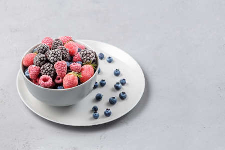 Frozen berries in a gray bowl on a gray concrete background. 免版税图像 - 155682591