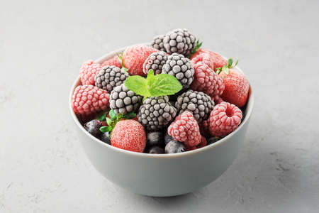 Frozen berries in a gray bowl on a gray concrete background. 免版税图像