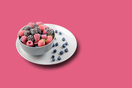 Frozen berries in a gray bowl on a pink background with copies of space.