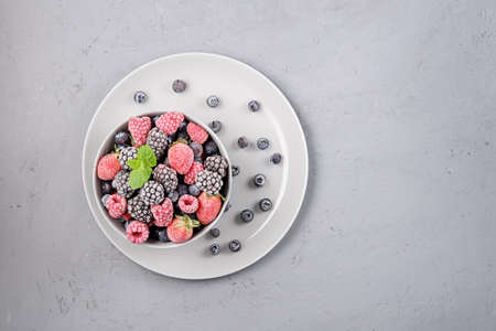 Frozen berries in a gray bowl on a gray concrete background with copies of space.