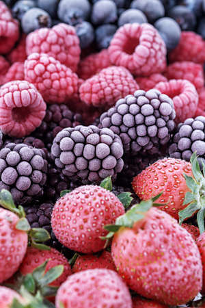 The frozen berries of raspberries, blackberries, blueberries, strawberries, covered with hoarfrost.