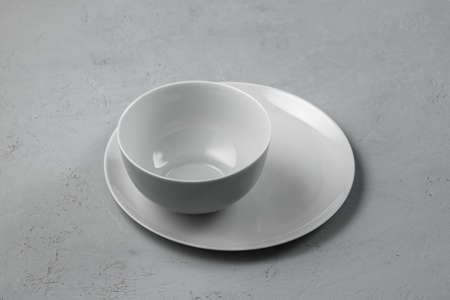 Bowl with a plate on a gray concrete background with a copy of space. 免版税图像 - 155505699