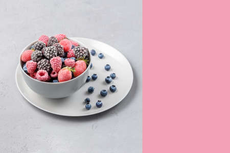 Frozen berries in a gray bowl on a gray concrete background. 免版税图像 - 155682828