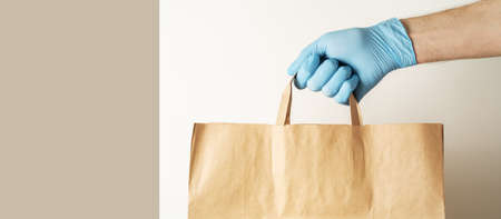 The concept of food delivery. A man's hand in medical gloves holds a paper bag. 免版税图像
