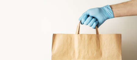 The concept of food delivery. A man's hand in medical gloves holds a paper bag. 免版税图像 - 155850178