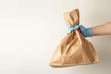 The concept of food delivery. A man's hand in medical gloves holds a paper bag. 免版税图像 - 155850183