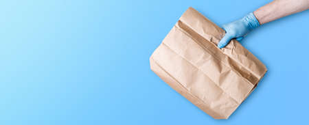 The concept of food delivery. A man's hand in medical gloves holds a paper bag against a blue background. 免版税图像