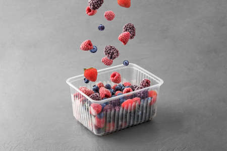 Frozen berries fall into a plastic box on a gray concrete background.