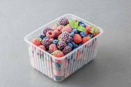 Frozen berries in a plastic box on a gray concrete background.