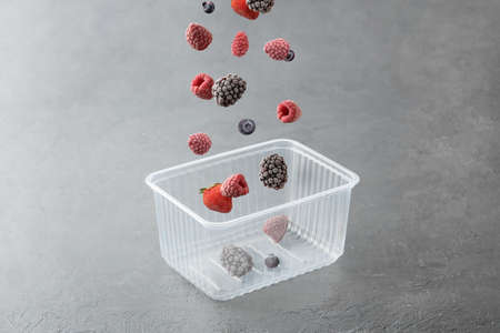 Frozen berries fall into a plastic box on a gray concrete background. 免版税图像 - 155928982