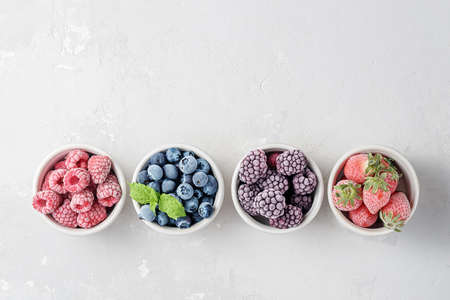 Frozen berries in small bowls on a concrete background from copies of space. 免版税图像 - 155928985
