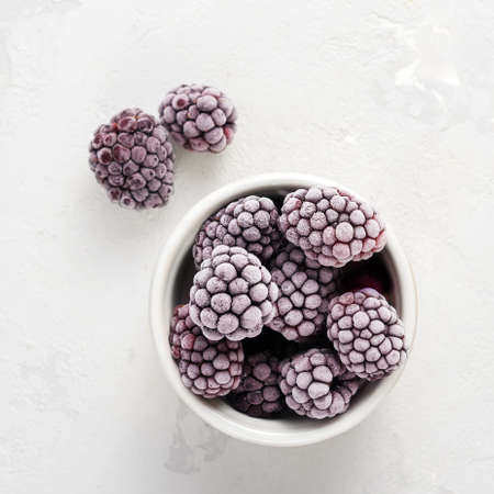 Frozen blackberries on a concrete background. Top view.