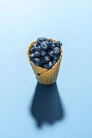 Frozen blueberries in waffle horn on a blue background. Conceptual minimalism. 免版税图像