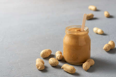 Homemade peanut butter in a glass jar on a concrete surface. 免版税图像