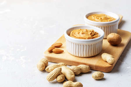 Peanut, almond and walnut butter on a concrete background.
