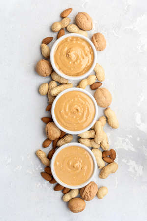 Peanut, almond and walnut butter on a concrete background. Top View