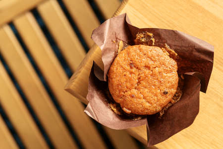 Yummy muffin on a wooden brown table with a copy of the space. Top view.