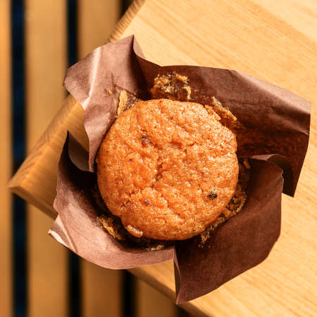 Yummy muffin on a wooden brown table. Top view. 免版税图像