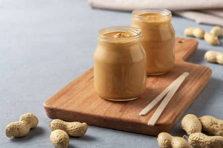 Homemade peanut butter in glass jars on concrete surface. 免版税图像